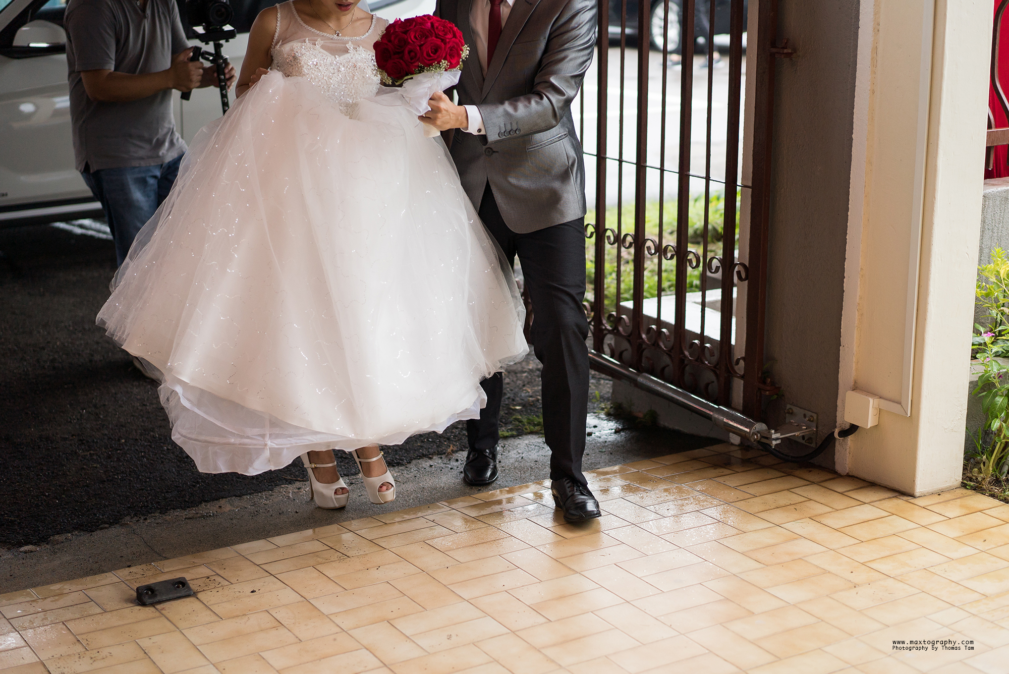 Bride and groom entering house gate