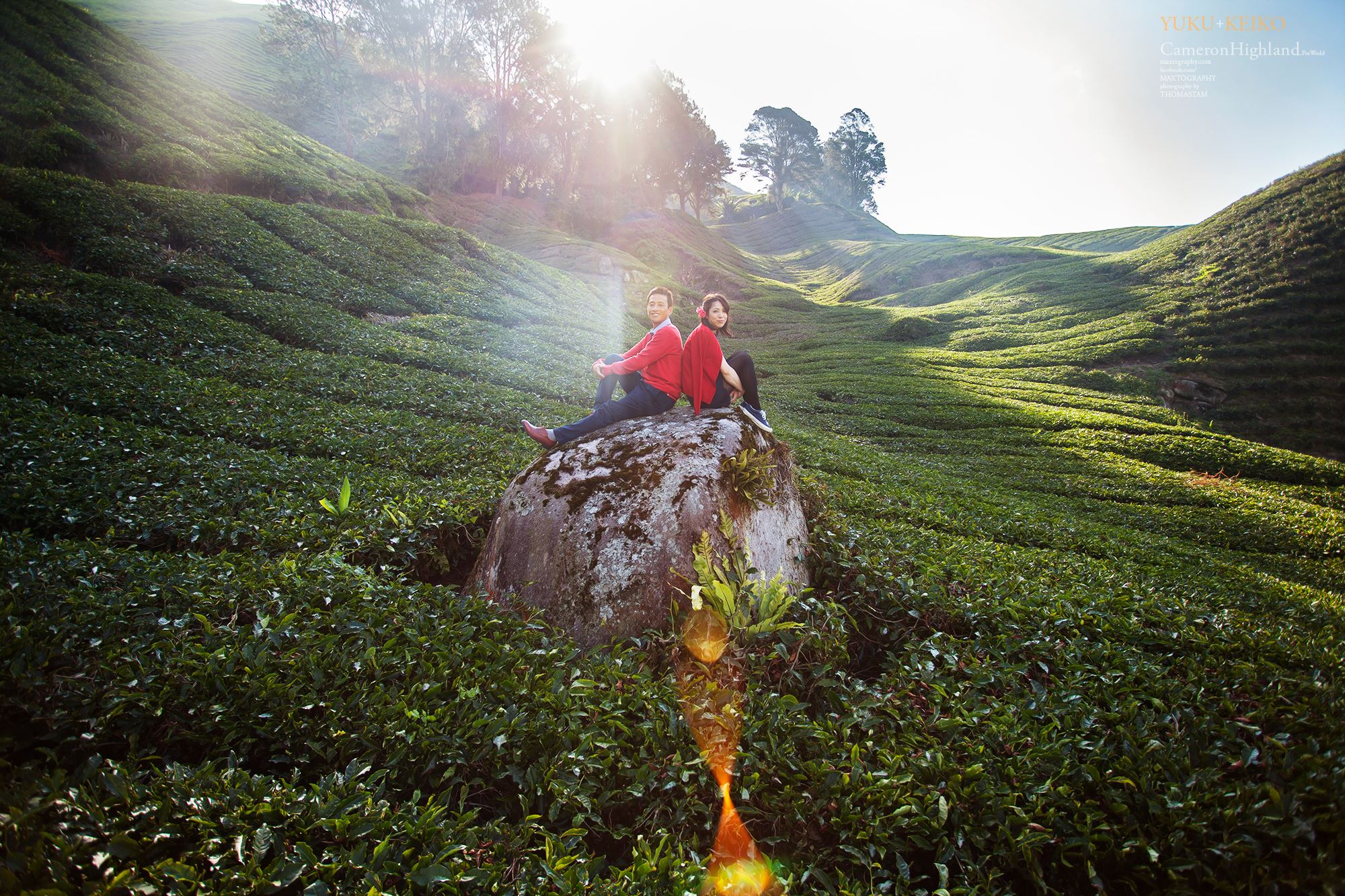 Couple sitting on the huge stone at Cameron Highland