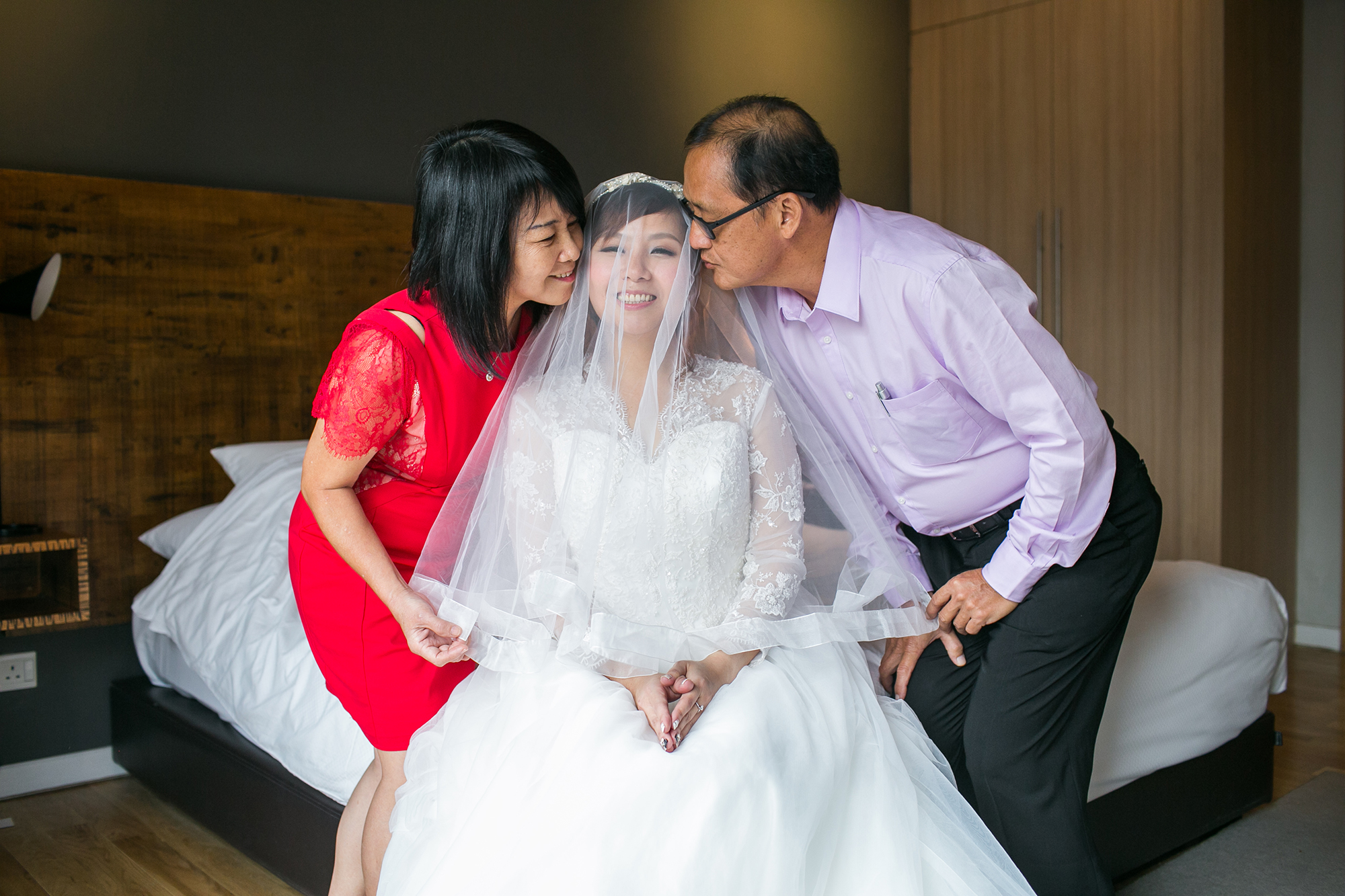 Parents kissing bride