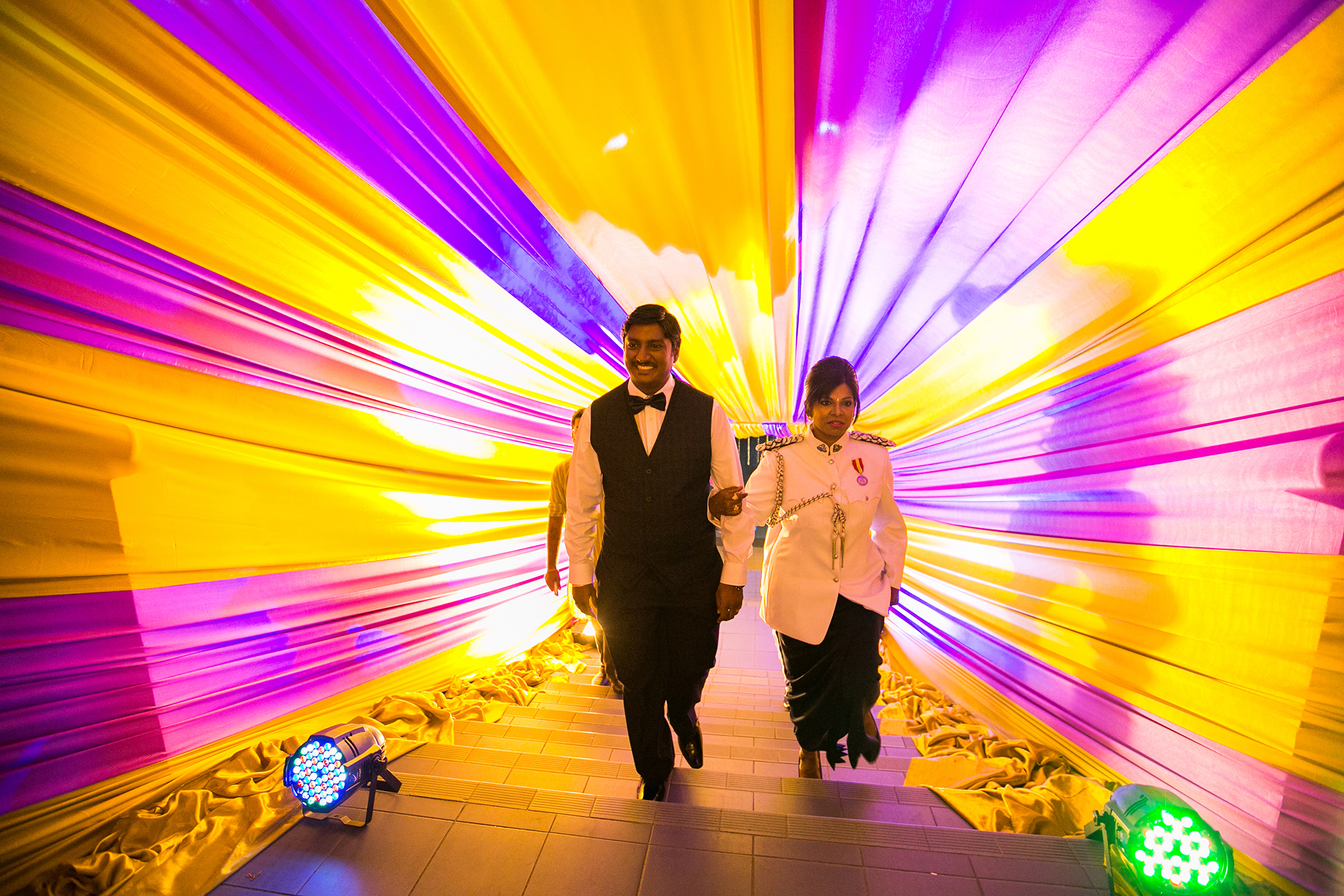 bride and groom march in thru the colourful tunnel