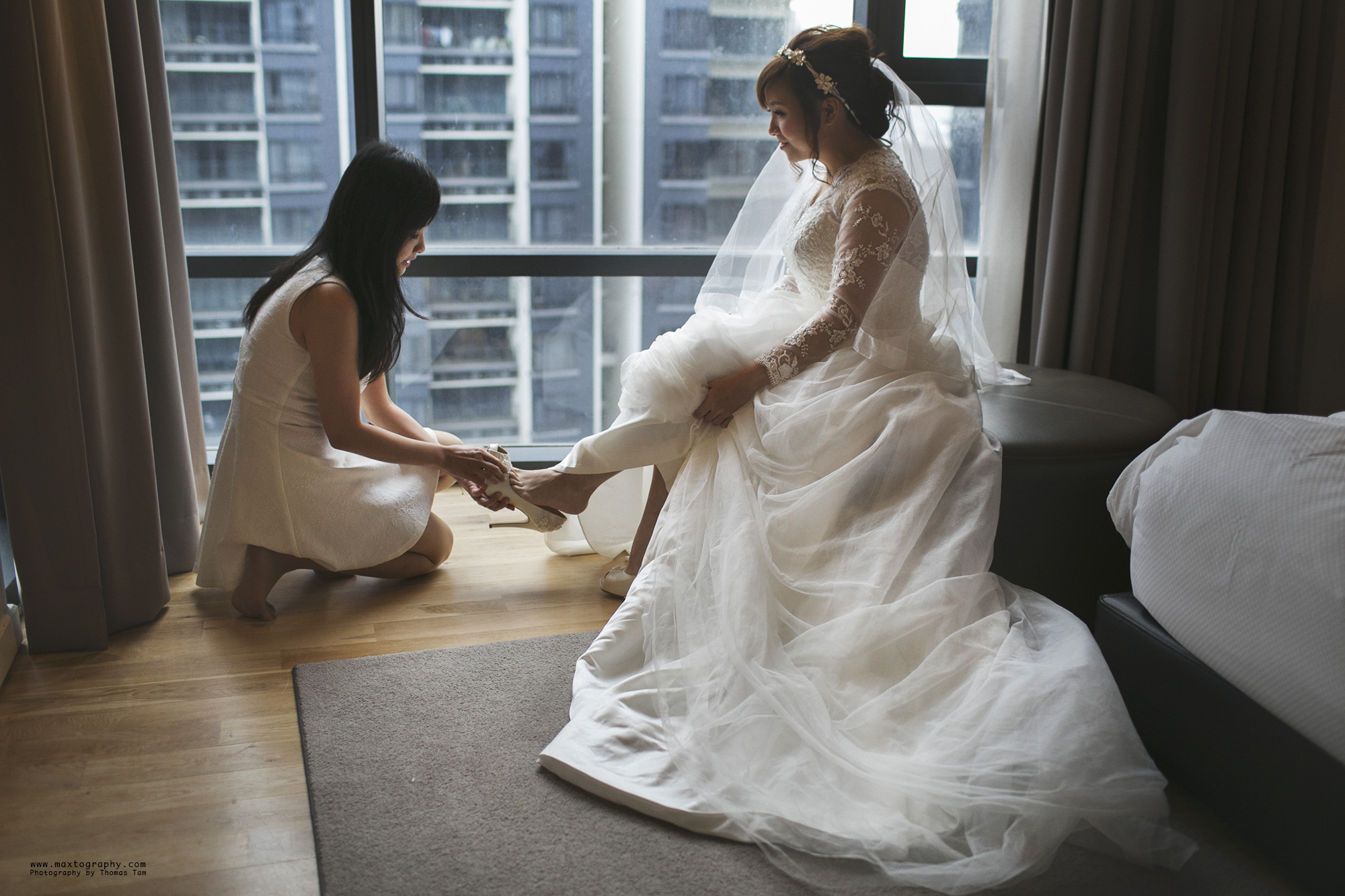 sister helping bride wear shoes