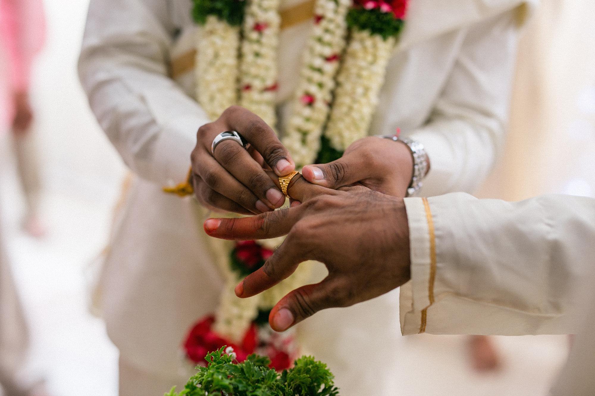 Groom wearing ring to groomsmaid