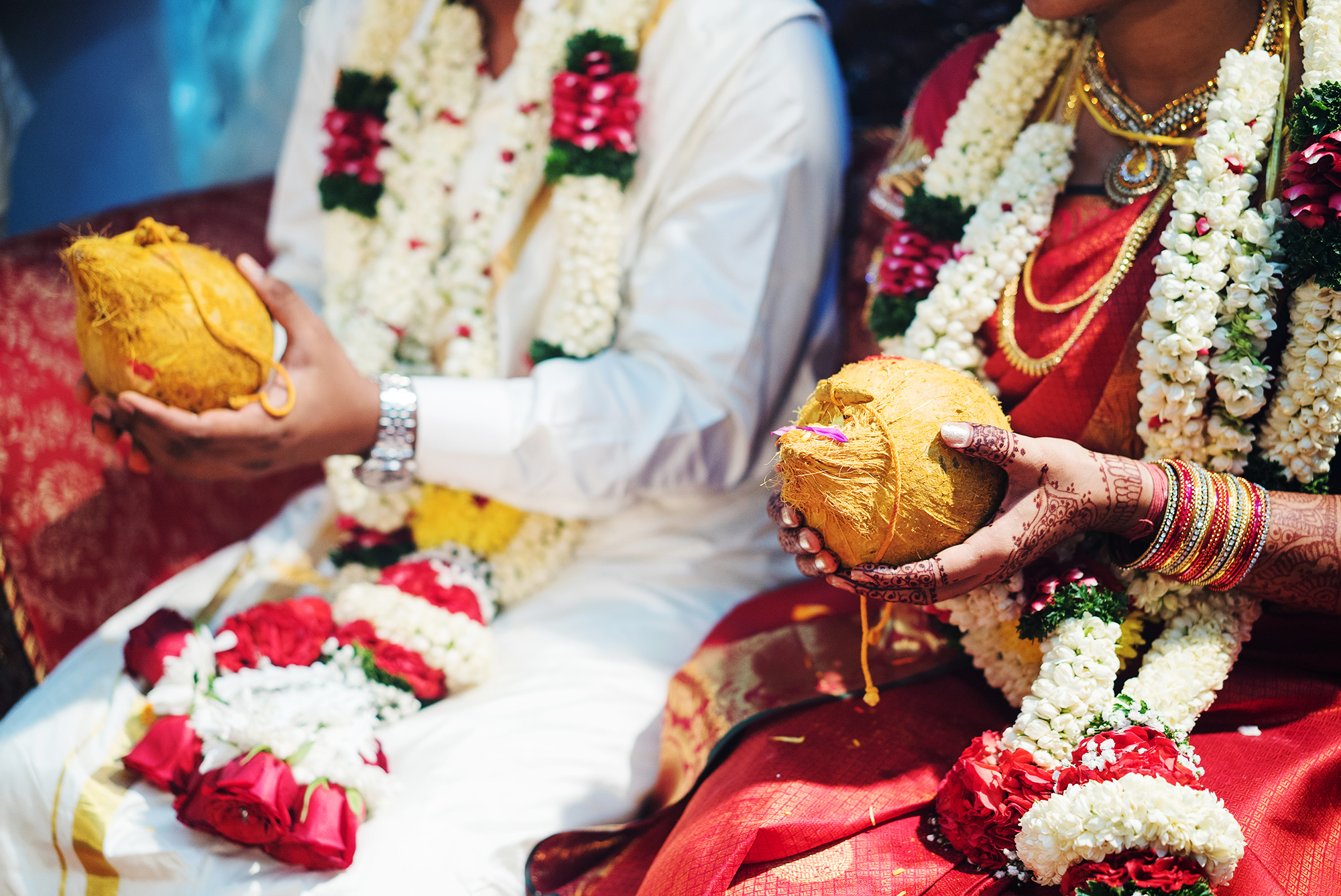 Hindu bride and groom holding coconut
