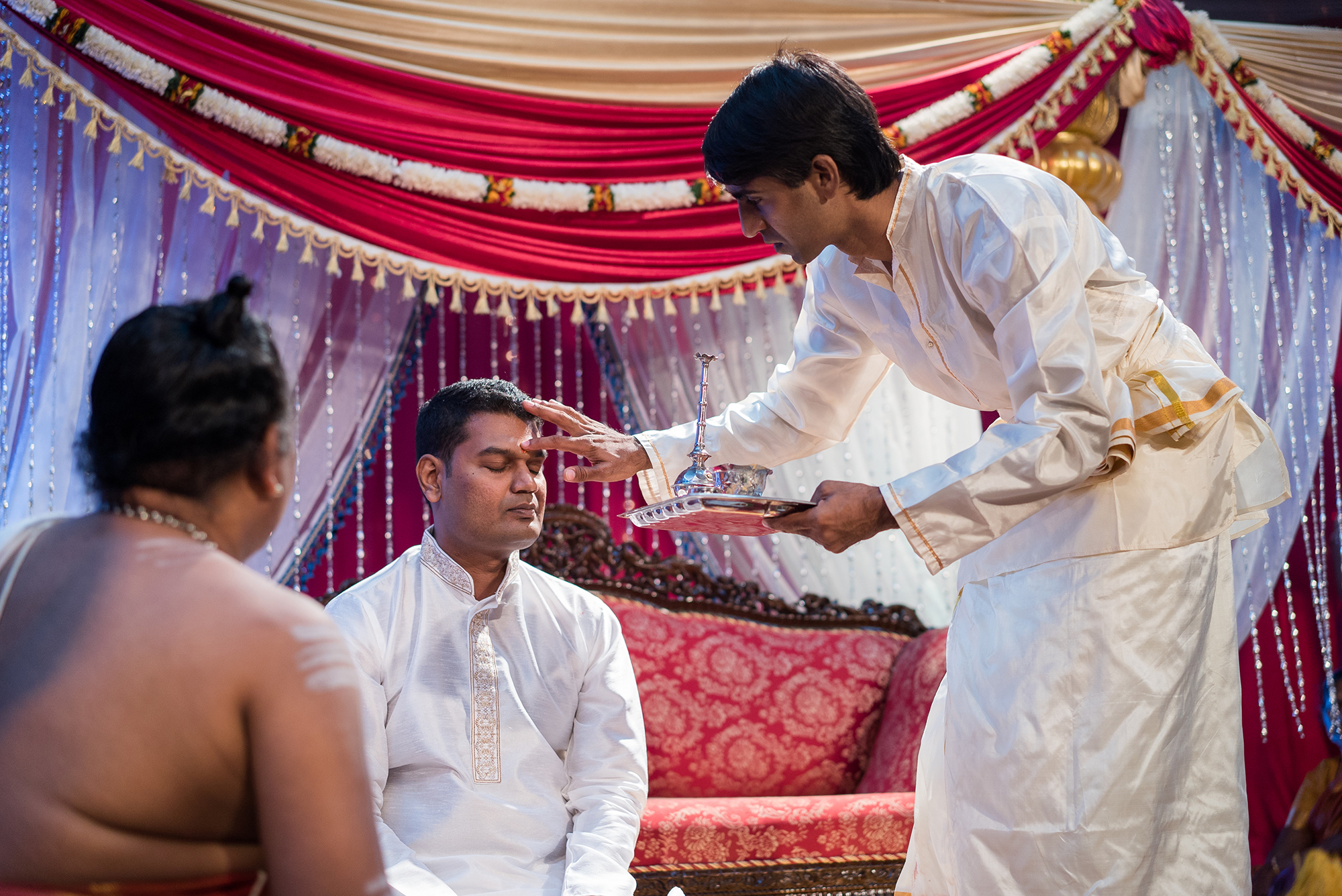 groom gets blessing by groomsmaid